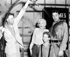 Marilyn Monroe, Tommy Rettig and Robert Mitchum get drenched in preparation  for a scene of River Of No Return.