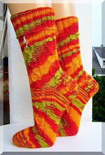 Die Wolle ist zu unruhig für das Muster, man erkennt die Zöpfe ja kaum noch. Außerdem: rot und orange.