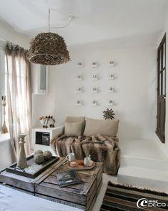 Dans un salon, quatre caisses à pommes en bois se détournent en table basse, suspension et grand plateau en bois 'Athezza', tapis rayé 'AM.P...