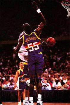 The GOAT glides to the hoop with the pressure from Dikembe Mutombo in Chicago.