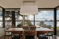 This dining room with a wood table has views of the water through the large picture windows. #DiningRoom #Windows