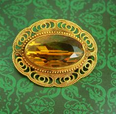 This gorgeous open back faceted glass brooch has gorgeous brass filigree around it that frames it so well. This is an early 1900's piece with C clasp and it is in very good condition.The color is golden topaz and it is even prettier than the photos. VintageSparkles offers Layaway on all our pieces regardless of which site it comes from.. Please remember that vintage & antique items are not mint, nor are they perfect but they sure are full of old history and charm. Please use photos to make…