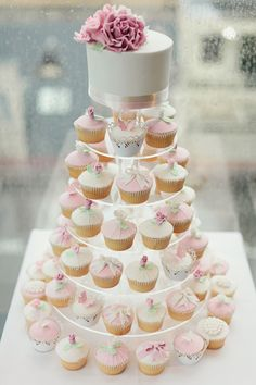 Wedding cup cakes are popular as a less expensive option but still having a small cake to cut as per tradition. The cupcakes do not need to be this fancy. I just pinned this for the cake and cupcakes together. They could just have plain icing if the table is decorated.