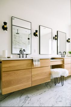 Floating white oak vanity with marble floors. Cambria Quartz weybourne countertops. Black faucets. Cedar and Moss sconces.