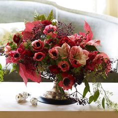 Pretty Christmas Flower Arrangement  Arrange a festive bouquet for the holidays with an assortment of poinsettias, begonia leaves, anemones, ranunculus, and amaryllis. For step-by-step instructions on how to create this arrangement, see the next slides