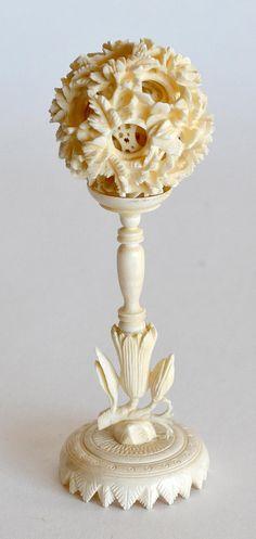 Petite BOULE de CANTON en ivoire sculpté et repercé, reposant sur un haut pied en ivoire tourné. H. 14 cm