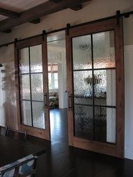 Designed by the architect this pair of track doors was built of blackened steel, water glass and reclaimed white oak. Each door is 4ft x 9ft and weights 280lbs. Track length is 19ft. Door handles were fabricated to match all with false hardware on both sides to allow the owners request that all bolts be aligned.