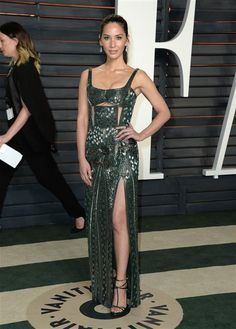 Olivia showed a lot more skin at the Vanity Fair Oscar Party, sporting a slinky, textured dark green gown with strategically placed cut outs on the bodice and a thigh-high slit.