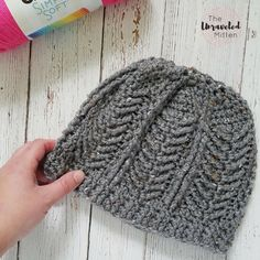 This crochet beanie was inspired by Michigan's Mackinac Bridge. It features sections of straight and diagonal post stitches that create a textured chevron pattern mimicking the columns and cables of this iconic bridge.