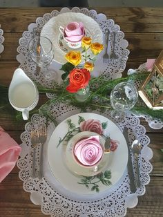 Vintage cream and sugar bone china with  custom rolled blush napkins in the shape of roses atop vintage China place settings and doilies amid a bed of North Carolina ferns on rustic wooden tables with tiny floral vases punctuating the setting