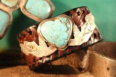 CHOCOLATE TOOLED LEATHER CUFF, TRIMMED IN WHIPSTITCHING WITH A STUNNING LARGE TURQUOISE HEART SET IN STERLING SILVER AND FLANKED BY TWO HAND SAWN SWALLOWS