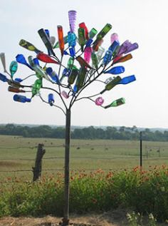 You can see bottle trees scattered all over the Southern landscape. Especially in Alabama, Louisiana, Mississippi & Tennesee ~ bottle trees are a colorful folk tradition with th (Bottle Display Country Living) Wine Bottle Trees, Wine Bottle Crafts, Bottle Art, Wine Tree, Ideias Diy, Found Art, Garden Features, Bottles And Jars, Glass Bottles