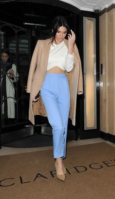 Kendall Jenner Street Style: See Her 20 Best Looks - pastel blue high-waisted trousers worn with a white long sleeve crop top + over-the-shoulder camel coat and nude pointy toe heels