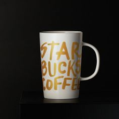 "A white ceramic coffee mug covered with ""STARBUCKS COFFEE"" in gold graffiti-style letters."