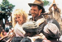 """Kate Capshaw as """"Willie"""" Scott, Harrison Ford as #IndianaJones & Jonathan Ke Quan as Short Round in the background in Temple of Doom (1984)"""