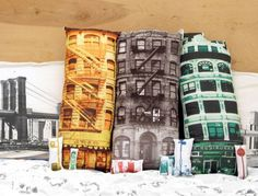 Build Your Block Pillows by Patrick Chirico.  Inspired by deli's, brownstones, and abandoned buildings that he walked past daily in his Brooklyn neighborhood, he translated the images into a pillow collection so that people could be urban planners or just lay their heads in the streets of New York City.