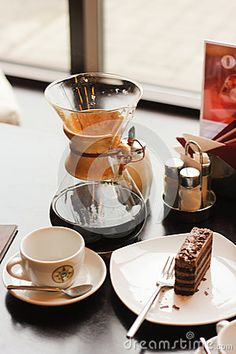Interesting coffee pot and chocolate dessert on the table in cafe