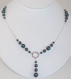 This beautiful necklace is handmade from graduated Tahitian Swarovski crystal pearls and sterling silver plated chain. Tahitian pearls are a dark gray color with deep green/blue overtones. Perfect for the office or to wear with a cocktail dress. It measures 19 in length, but the clasp can be repositioned along the chain to adjust the length to accommodate different necklines. It features a sterling silver lobster claw clasp and other sterling components.  This would be a stunning gift and…