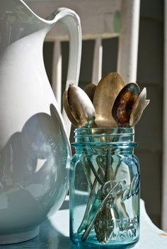 Love the combination of white pitcher, blue canning jar, and tarnished spoons.