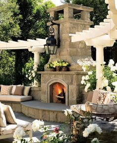 This has always been one of my favorites exterior fireplaces - love the large lantern, mantle to decorate, large hearth to sit on and enjoy the fire, cushioned seating next to the fireplace, the trellis -- all perfect