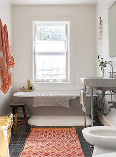 Orange fouta towels and a geometric rug add a splash of color to the kids' bathroom.