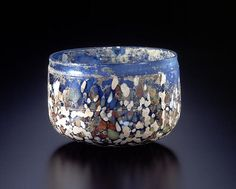 Roman Splash Glass, 1st century C.E. white, yellow, red and pale blue glass has been scattered over a semi-translucent blue bowl. The decorative dots of glass are thinly fused onto the walls and built up into thicker deposits on the base. The bowl's inner surface and mouth area has been finished with a grinder or a file, after the splash decoration was applied, a single cord-shaped decoration was carved around the center of the exterior of the bowl. Miho Museum Kyoto, Japan