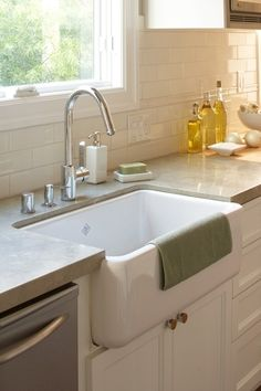 white porcelain farmhouse sink, white flat panel kitchen cabinets, gray quartz countertops and subway tiles backsplash