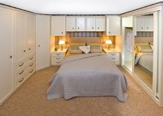 Calming creams and ivories. Overbed storage maximises space in the bedroom.
