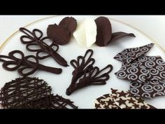 Video:  how to make chocolate garnishes decorations tutorial PART 2 - Ann Reardon - Ep022 Make chocolate flourishes, paint the back of leaves, Using a small swirl template, put one color, freeze, layer a different color over top.  Make a circle mold, by cuttinn out circle on a sheet of heavy plastic, layer chocolate strings in both directions and while still melted, remove plastic mold, freeze.