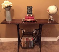 Singer sewing machine console table - I used the wrought iron base of a Singer sewing machine, and my favourite colour of stain (Jacobean) for the wooden tabletop. Finished off with rope trim ~The Decor Vault~