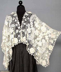 "Irish crochet shaped shawl, c1915. Shamrock, flower and foliage patterned lace, falls below hip in front and to waist in back, Center front length 19"", Center back length 23.5"""