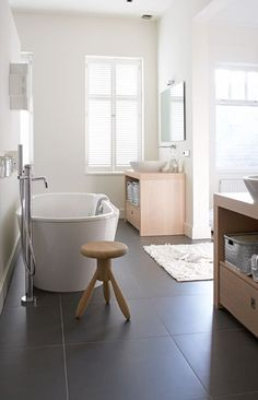 White walls, large grey floor tiles, nice w timber and white bath Ruimtelijk en open - vtwonen Grey Flooring, Laundry In Bathroom, House Bathroom, Home, Tile Floor, Bathroom, Black Bathroom Floor, Bathroom Flooring, Bathroom Inspiration