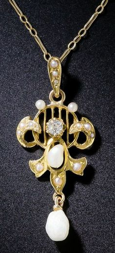 American Art Nouveau Pearl and Diamond Pendant. A lovely example of American Art Nouveau. This fourteen karat yellow gold pendant dates back to the turn of the last century. Inspired by the French Art Nouveau movement, the pendant incorporates the traditional movement created by flowing curves, but this one is accented with fresh water pearls found exclusively in the Mississippi River Delta. A European-cut diamond is prong set on the upper half of the pendant