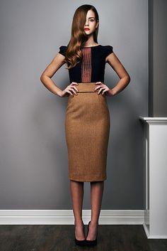Perfectly pristine. Curled hair, long brown pencil skirt, silk sheer black top.