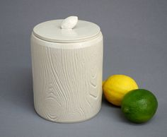 Both stylish and whimsical, this cylindrical faux bois jar will complement any decor. The wood grain pattern is impressed into the clay, and the lid