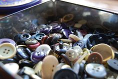 Playing with the buttons in mum's button tin while she was sewing.