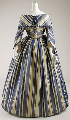 American navy blue and cream striped silk dress (circa 1854). Pre-Civil War, this dress displays the full gathered skirt worn over a hooped crinoline. Portrait neckline with shawl-like collar.