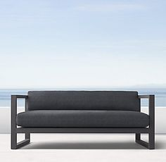"""RH's 64"""" Aegean Aluminum Sofa:Influenced by the low, linear silhouettes of seaside architecture, our contemporary collection is designed by a family-owned company in Australia known for its meticulous metalwork. Its superior materials and simple geometry enable it to weather the elements in enduring style. WATCH THE FILM """"BENDING THE TUBE"""" FEATURING THE CONDOS BROTHERS ▸"""