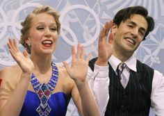 Kaitlyn Weaver and Andrew Poje of Canada wave to spectators as they wait in the results area after competing in the ice dance short dance fi...