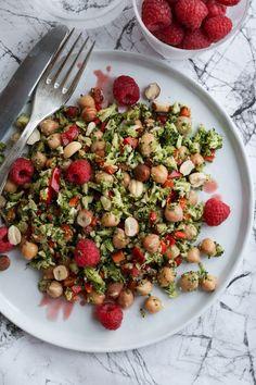 Vegetarisk broccolisalat med kikærter, peberfrugt og friske hindbær i en dressing af hasselnøddeolie og hindbær-balsamico. Toppet med ristede hasselnødder.