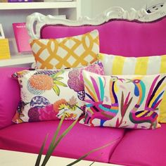 Pink couch with fun pillows.