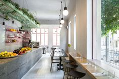 Amit Design Studio has recently completed Bana, a modern cafe that's located in Tel Aviv, Israel, and has design features like pink metal grid shelving and a large basket that hangs from the ceiling. Restaurant Interior Design, Cafe Interior, Tel Aviv, Houses In Poland, Metal Grid, Lokal, Wood Counter, Table Seating, Cafe Restaurant