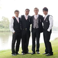 The groom wears a classic black suit, a white shirt and a silver best and teamed with a pale pink tie. Groomsmen wear black and pink