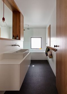 Bathroom Tile Ideas - Grey Hexagon Tiles | Dark grey hexagonal penny tiles cover the floor of this bathroom, contrasting the white and wood and adding a modern touch to the bright space.