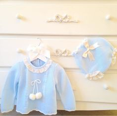 'Tami', blue knitted jumper, bottoms and bonnet with Pom poms, frills and satin bows. Available to purchase at bellaandlucella.com