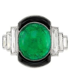 Platinum, Cabochon Emerald, Black Onyx and Diamond Ring. Centring one oval cabochon emerald approximately 4.50 cts., edged by two curved black onyx panels, flanked by six baguette diamonds, circa 1930.