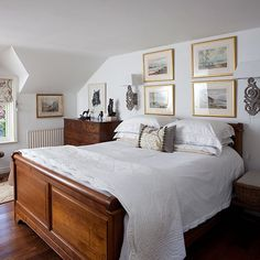 Pine double bed with white bedding in front of white wall