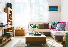 Essa sala de estar com jeito de praia abusou das cores e dos móveis de madeira.