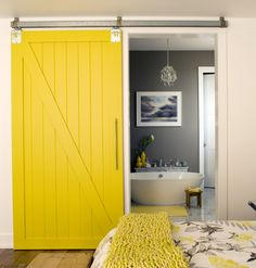 I love this bathroom barn door. The bright yellow pops against the bathroom's slate gray. Barn doors save space and are a gentle aproach to an industrial feel. #barndoor #yellowandgray #industrial