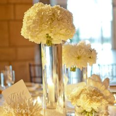beautiful white hydrangea centerpiece in tall cylinder vase along with smaller cylinder vases containing white dahlias and football mums